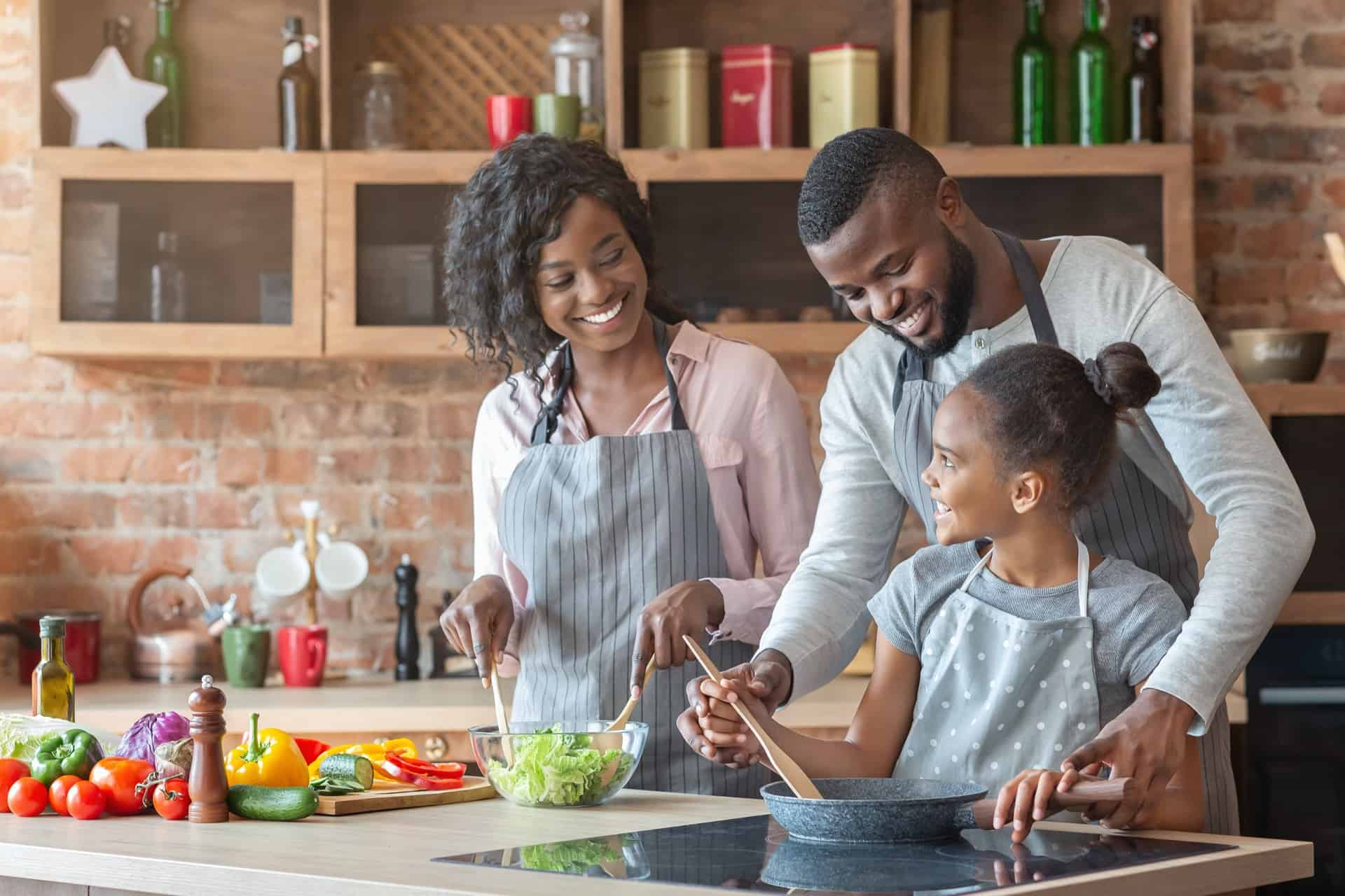 young parents teaching daughter how to cook QTLZGW8 - 5 Things You Can Do At Home With Your Kids